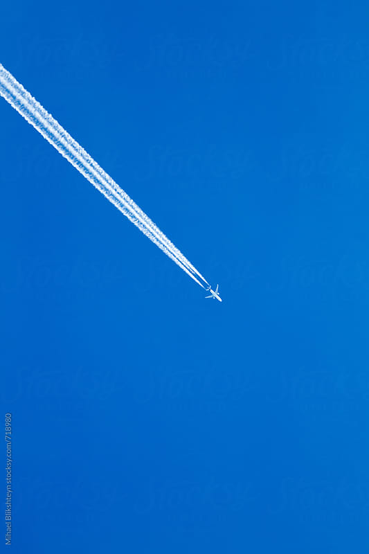 White contrail and tiny airplane against blue sky on a sunny day looking up by Mihael Blikshteyn for Stocksy United