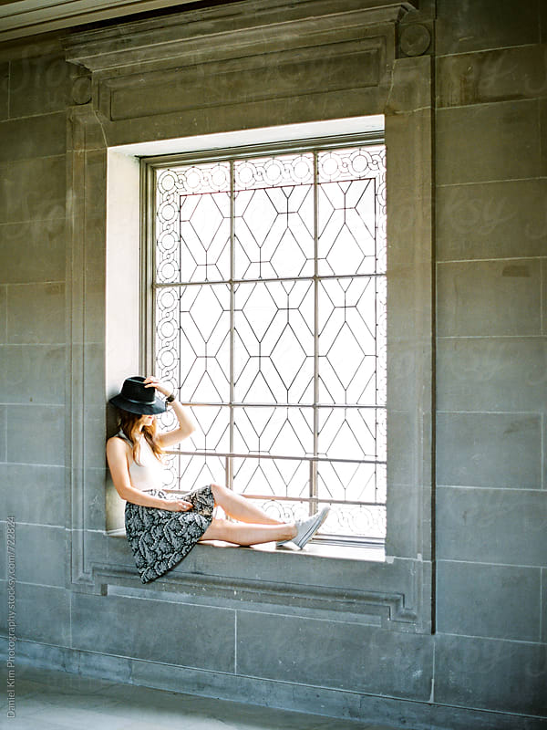 Woman sitting in pretty window by Daniel Kim Photography for Stocksy United