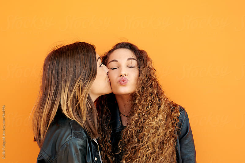 Side view of girl kissing her best friend with curly hair by Guille Faingold for Stocksy United