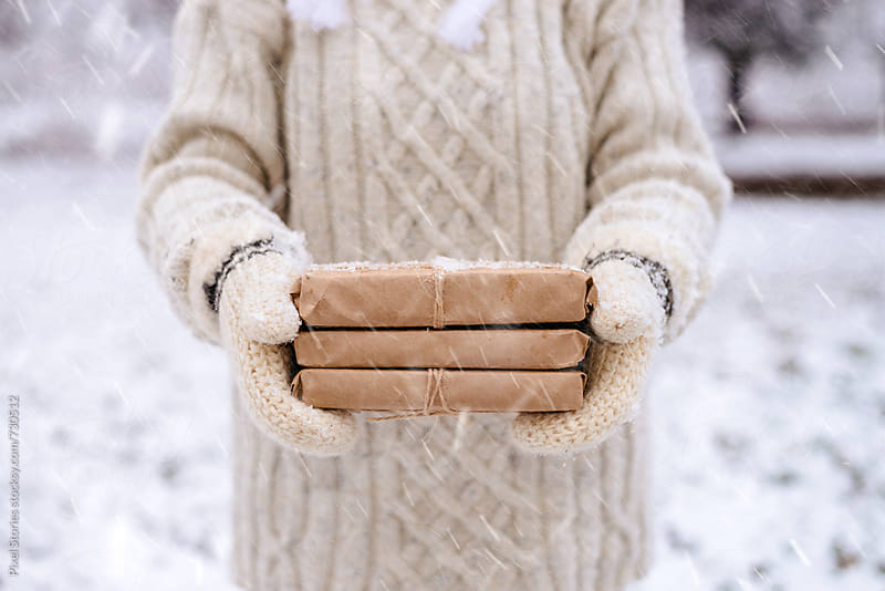 Woman holding rustic gifts in the snow by Pixel Stories for Stocksy United