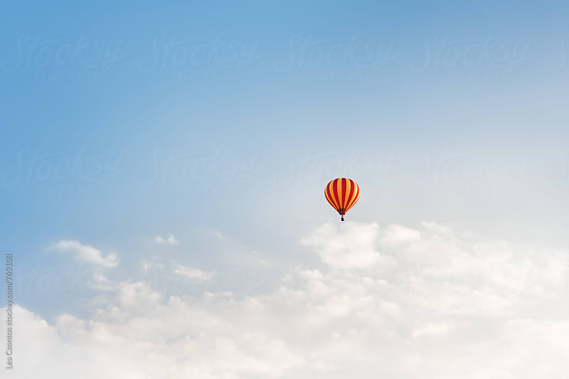 Lonely hot air balloon floating on the sky above the clouds by Lea Csontos for Stocksy United