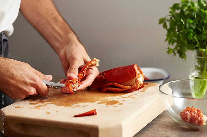 Man cutting lobster with clippers by Martí Sans for Stocksy United