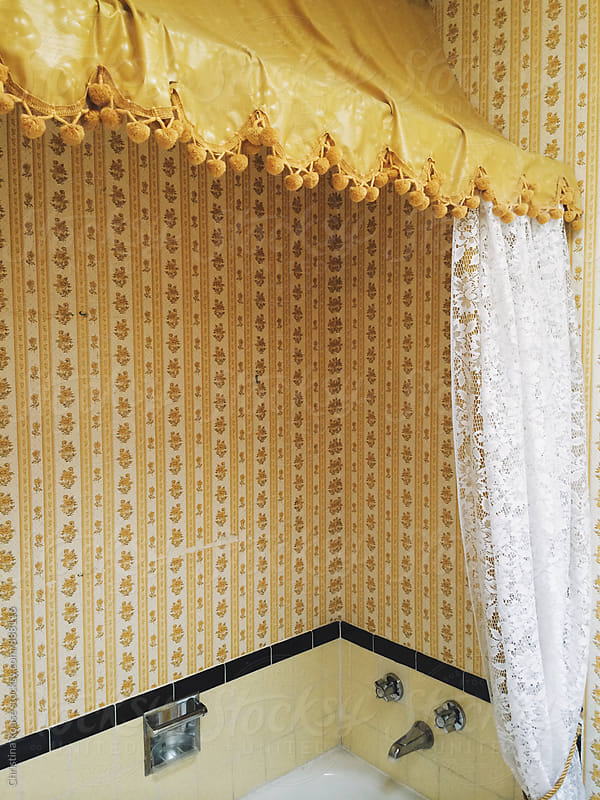 Outdated yellow bathroom with wallpaper by Christina Rouse for Stocksy United