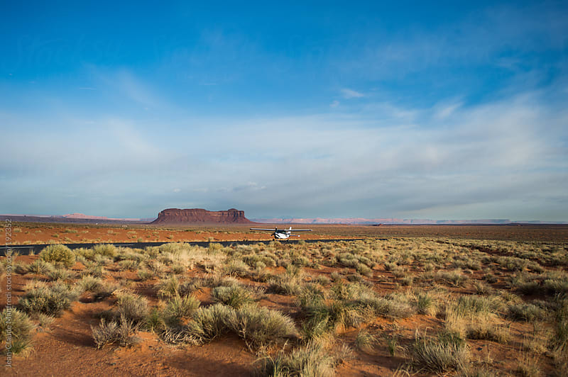 Landing of a small plane in the monument valley landscape by Jean-Claude Manfredi for Stocksy United