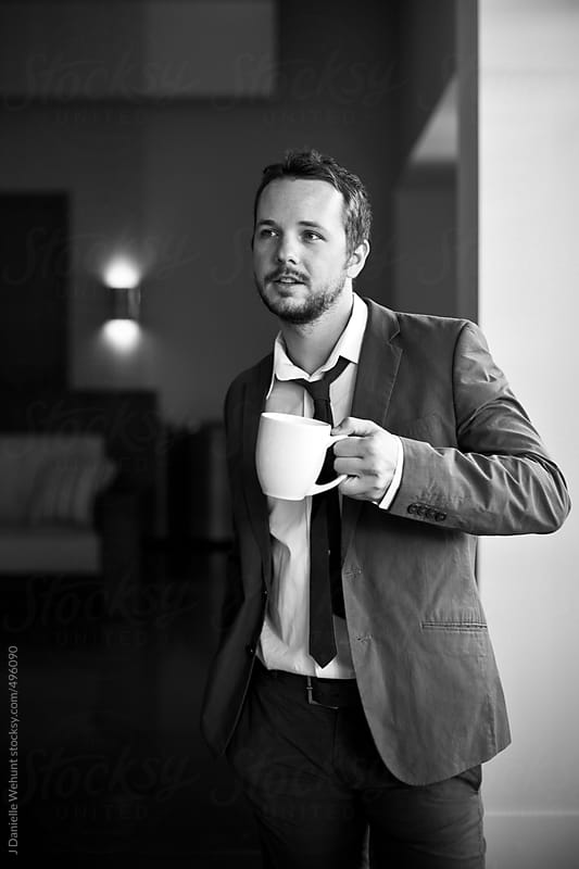 Business man in suit standing with coffee cup by J Danielle Wehunt for Stocksy United