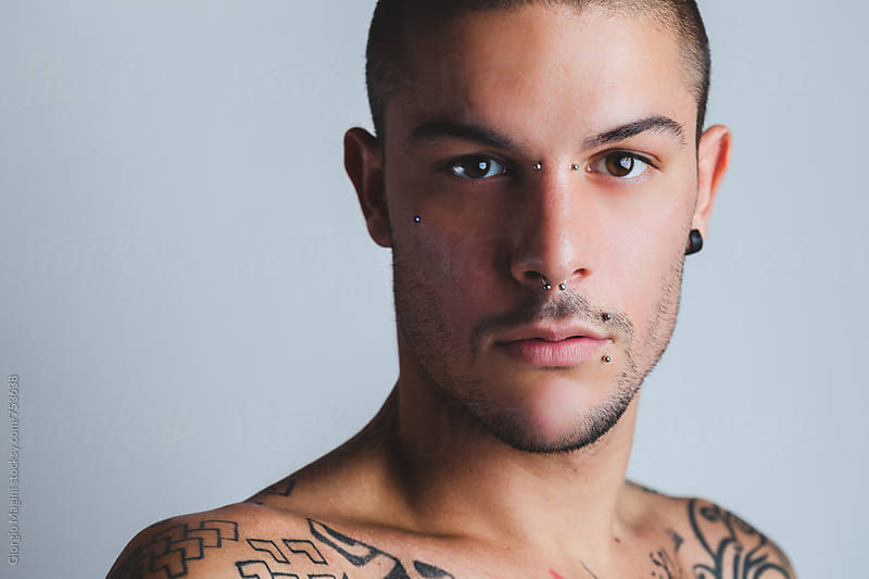Studio Portrait of a Sexy Young Man with Piercings and Tattoos by Giorgio Magini for Stocksy United