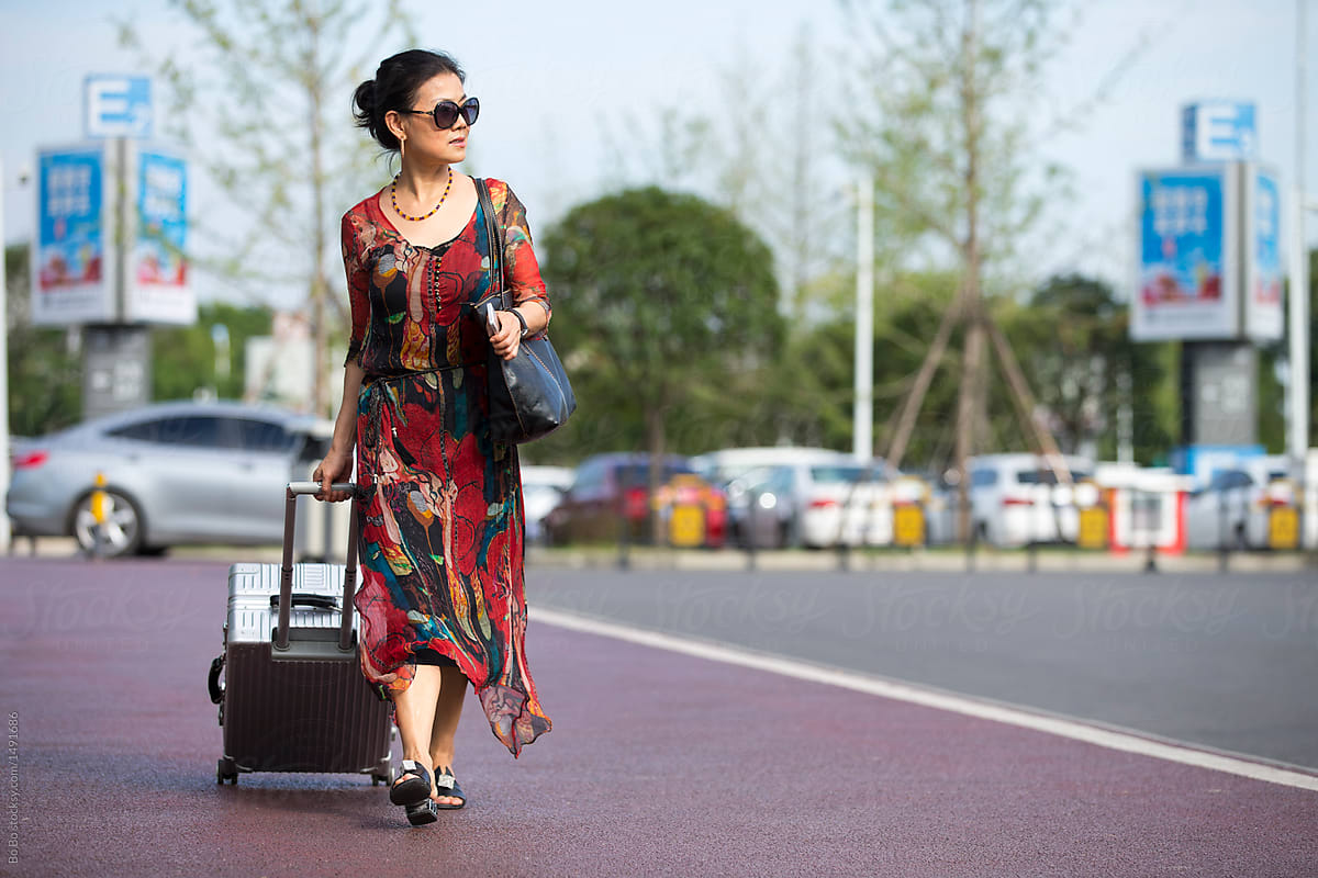 One senior asian woman traveling in airport by Bo Bo - Stocksy United