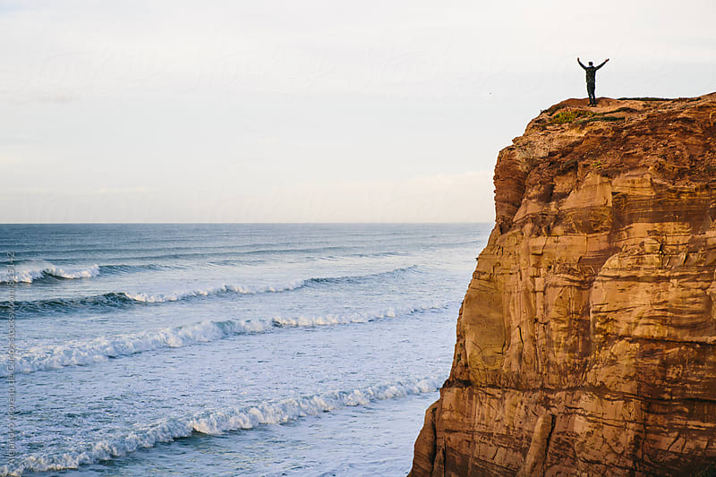 Free person on top of a cliff with his arms in the air in front of the ocean by Alejandro Moreno de Carlos for Stocksy United