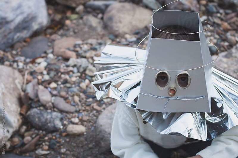 Boy wearing a homemade robot mask outdoors by Beatrix Boros for Stocksy United