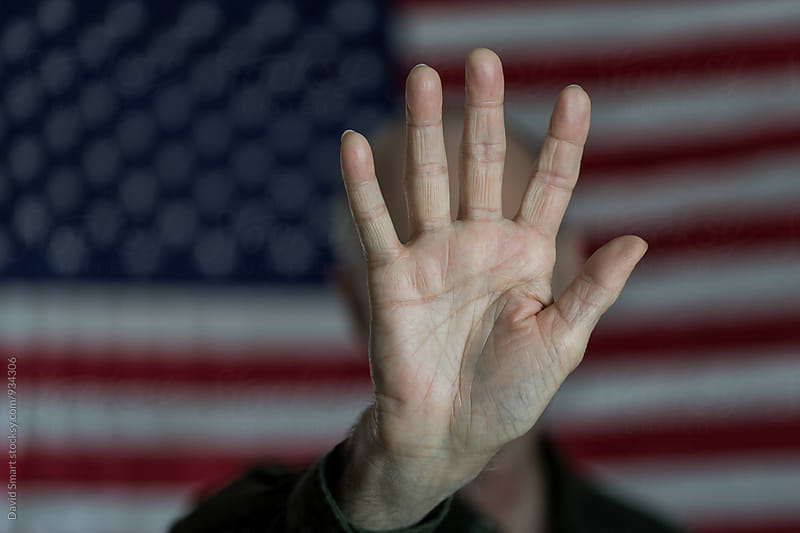 Hand of a senior white male signaling stop in front of an American flag by David Smart for Stocksy United