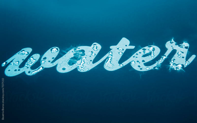 Word water written with wet cursive letters by Beatrix Boros for Stocksy United