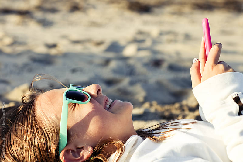 Girl on her electronic device texting at the beach and smiling by Carolyn Lagattuta for Stocksy United