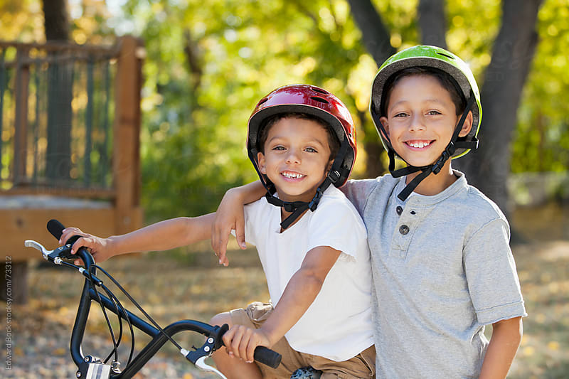 Two brothers wearing bicycle helmets pose together in the yard. by Edward Bock for Stocksy United