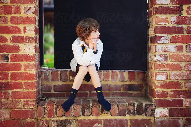 Boy in school uniform sitting in a doorway after school by Angela Lumsden for Stocksy United