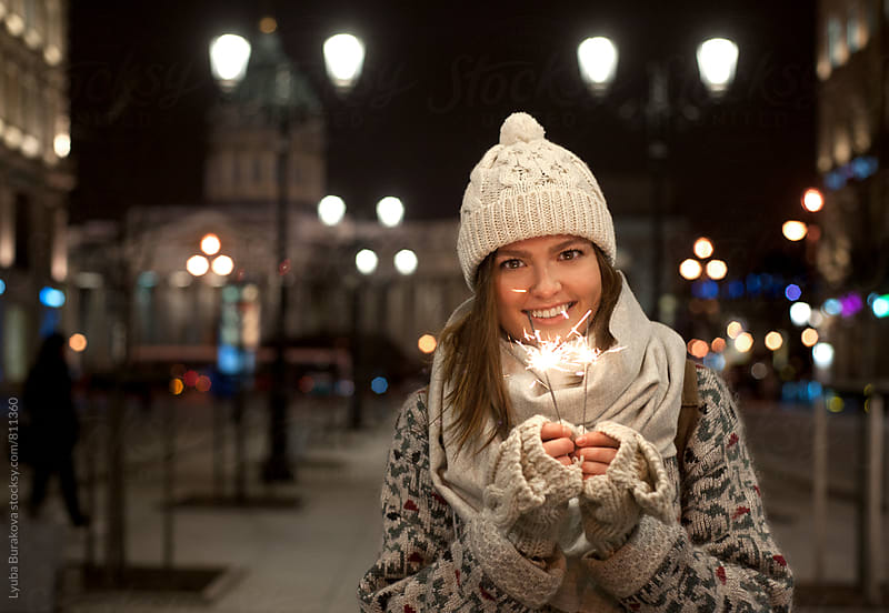 Portrait of young woman holding sparklers by Liubov Burakova for Stocksy United