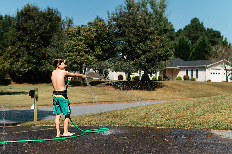 boy in swimsuit spraying water hose by Jess Lewis for Stocksy United