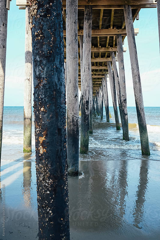 Wooden beams on underside of fishing pier by ocean by Kerry Murphy for Stocksy United