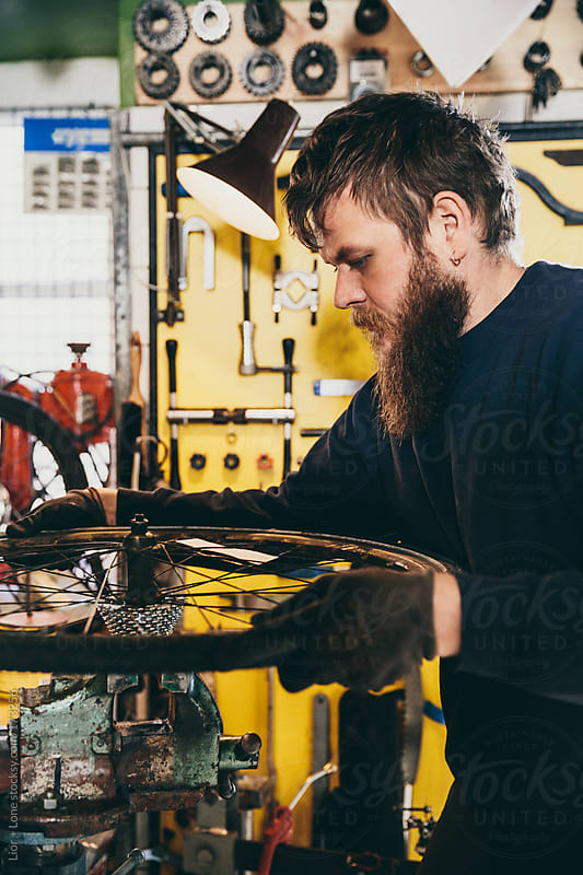 Young mechanic working on a wheel on a clamp by Lior + Lone for Stocksy United