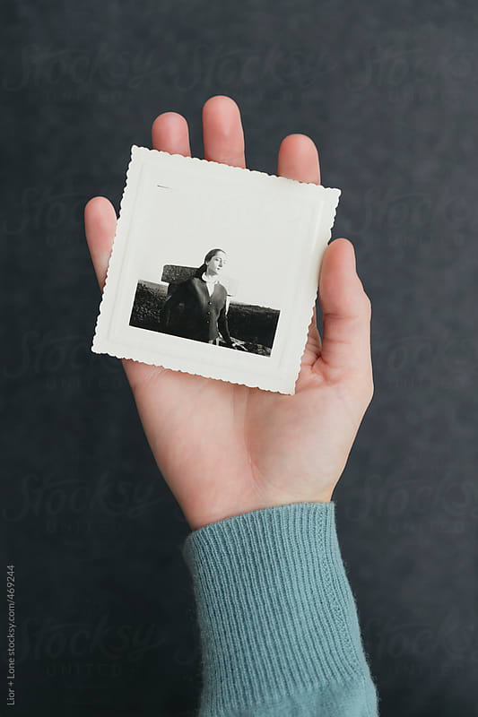 Closeup of hand holding vintage photograph by Lior + Lone for Stocksy United