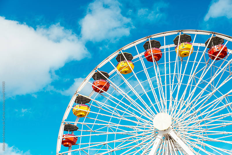 Detail of colourful ferris wheel against blue sky in summer by Alejandro Moreno de Carlos for Stocksy United