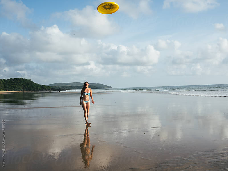 Girl in swimsuit throwing frisbee on the beach by Martin Matej for Stocksy United