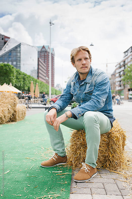 Young man sitting on a hay bale with a straw in his mouth by Koen Meershoek for Stocksy United
