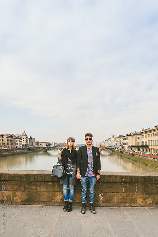Urban Teen Couple Standing Serious on a Bridge by Giorgio Magini for Stocksy United