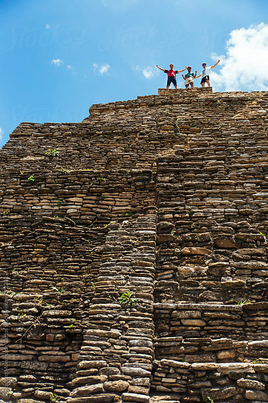 Three victorious men at the top of ancient pre-columbian ruins by Alejandro Moreno de Carlos for Stocksy United