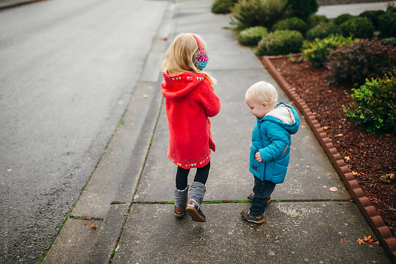 Two young Siblings walk Down the Sidewalk together in Winter Coats by Amanda Voelker for Stocksy United