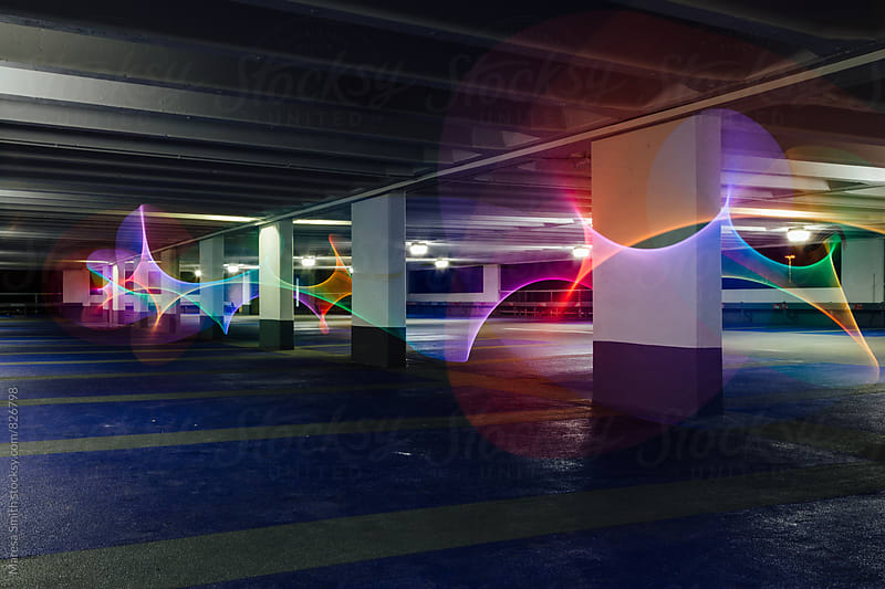 Rainbow swirls of light in an empty carpark at night by Maresa Smith for Stocksy United