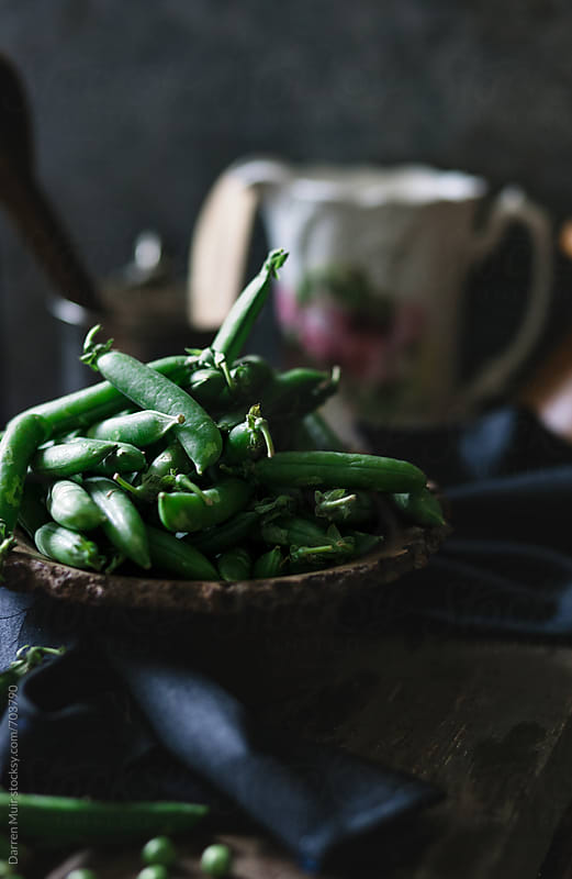 Garden peas in a wooden bowl in a rustic table setting. by Darren Muir for Stocksy United