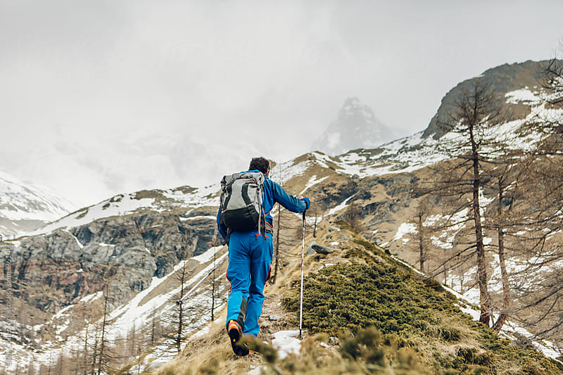 Young alpine climber with blue dress walking up to the glacier in the Italian Alps by Blue Collectors for Stocksy United