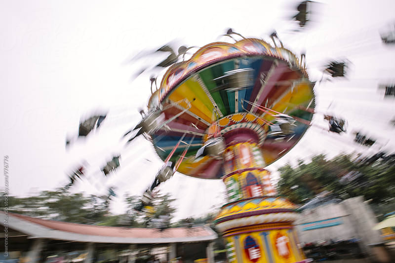 Blurry photo of an amusement park ride by Lawrence del Mundo for Stocksy United