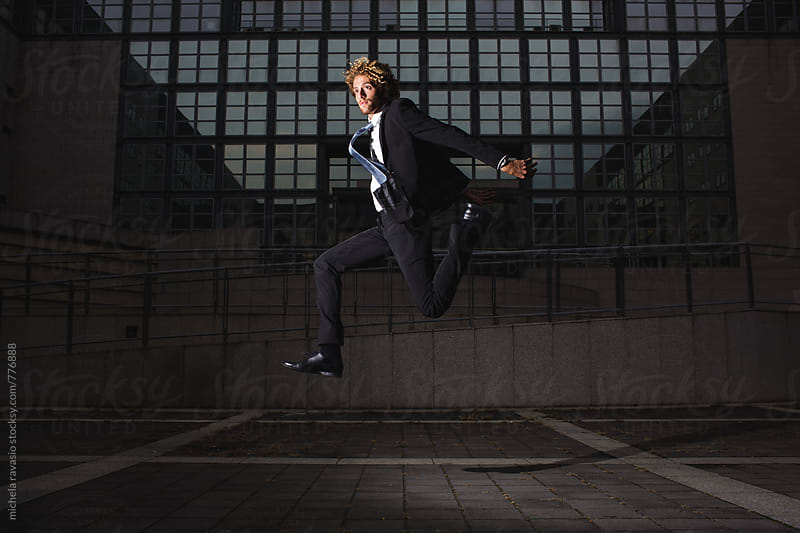 Young businessman jumping in the air by michela ravasio for Stocksy United