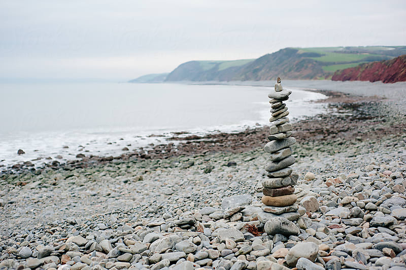 Cairn on a pebbly beach in Winter by Suzi Marshall for Stocksy United
