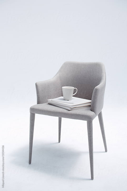 Chair, books and coffee with a white background by Miquel Llonch for Stocksy United