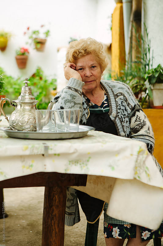 Senior woman  sitting at a table in a typical andalusian patio by kkgas for Stocksy United