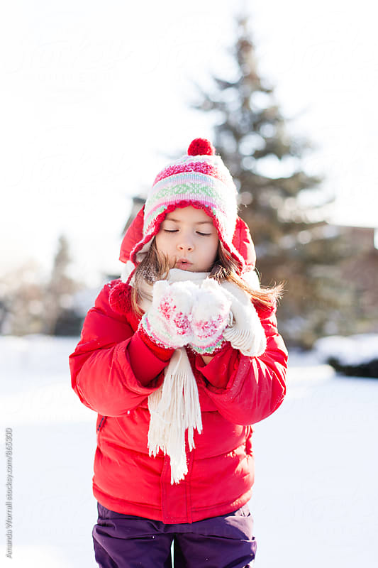 Young girl trying to blow snow from her colorful mittens by Amanda Worrall for Stocksy United