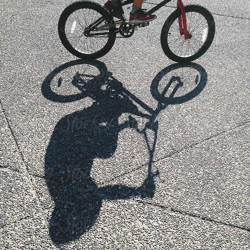 Shadow Of Child Riding Bike by Ronnie Comeau for Stocksy United