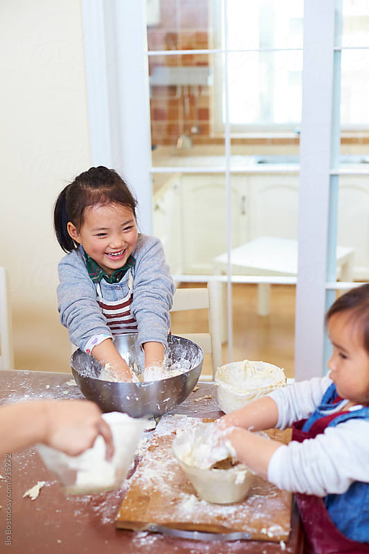 little asian girls having fun in kitchen by cuiyan Liu for Stocksy United