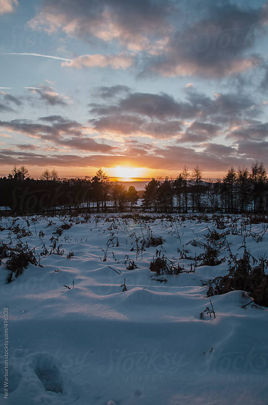 Sunset over snowy landscape by Neil Warburton for Stocksy United