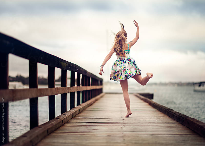 Young girl dancing on a dock above a river on a cloudy day by Angela Lumsden for Stocksy United