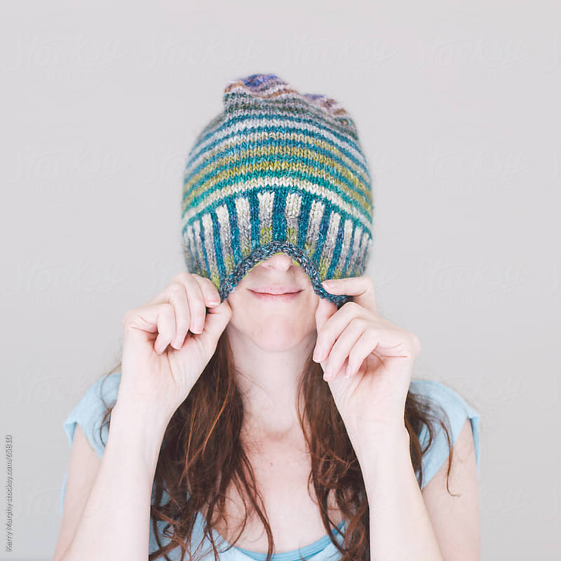 Woman Covering Face With Hand Knit Hat by Kerry Murphy for Stocksy United