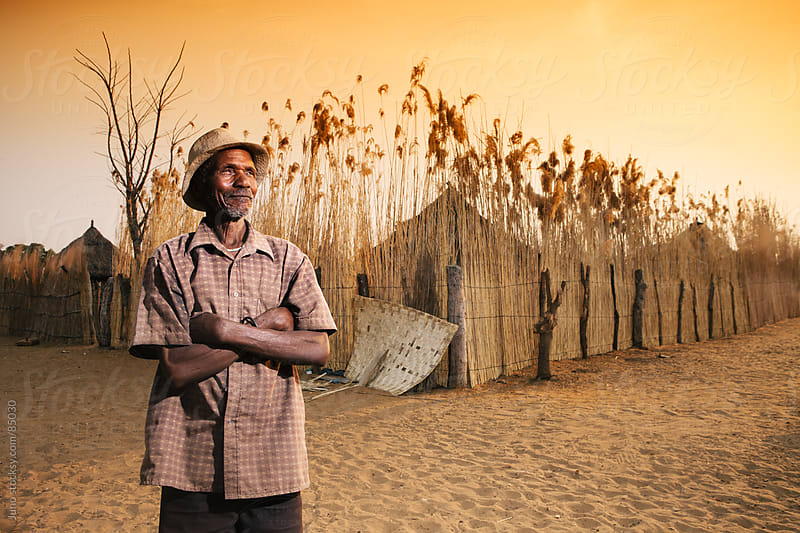 Portrait of an African Hambukushu man outside his village by Micky Wiswedel for Stocksy United
