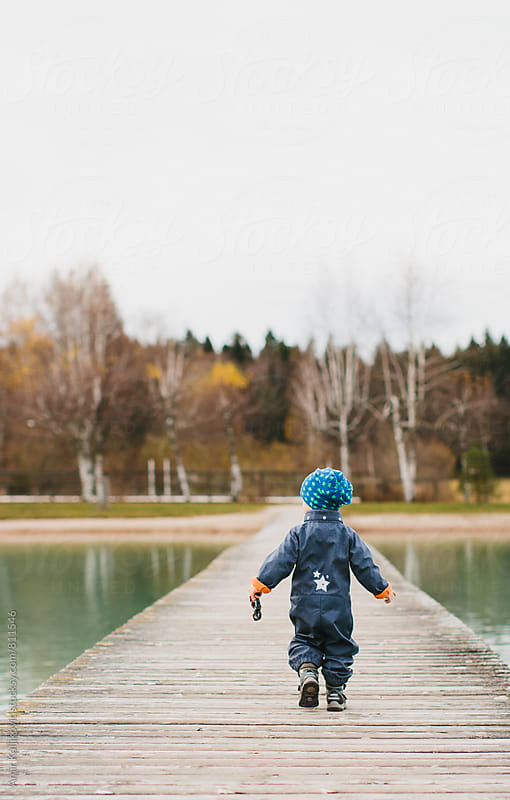 Small boy walking on a landing stage. by Amir Kaljikovic for Stocksy United