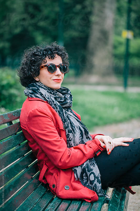 Relaxed Young Woman Sitting On A Bench by Davide Illini for Stocksy United