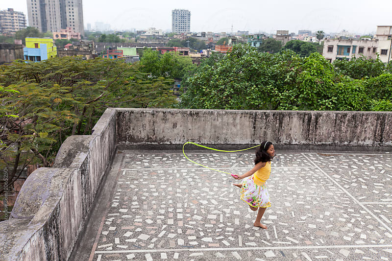Teenage girl playing and making fun with jumping rope at rooftop by PARTHA PAL for Stocksy United
