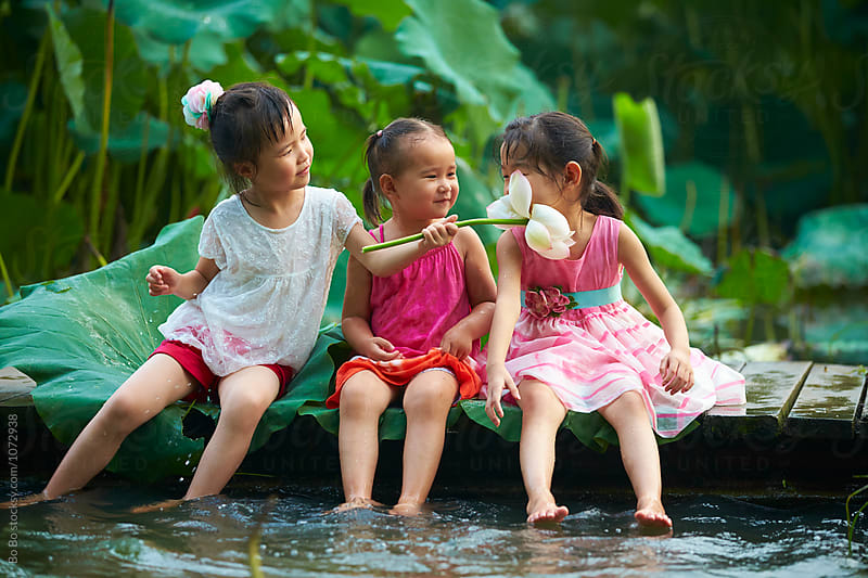 three little asian or CHinese girl playing water by the pond side by Bo Bo for Stocksy United