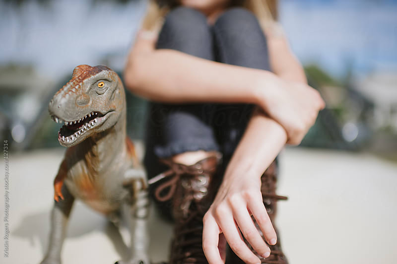 Young girl sitting next to her pet toy dinosaur by Kristin Rogers Photography for Stocksy United