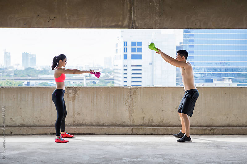 Young man and a woman working out with kettlebells with the city in the background  by Jovo Jovanovic for Stocksy United